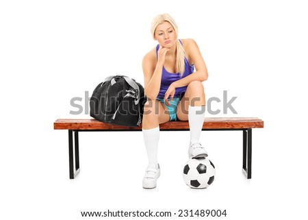 Worried female football player sitting on a bench isolated on white background - stock photo