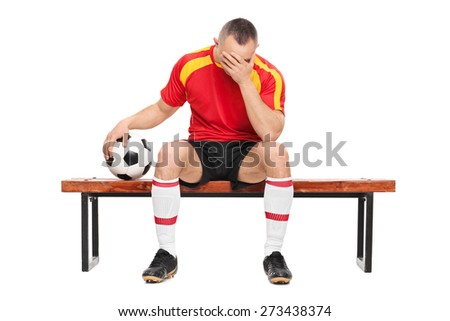 Worried football player sitting on a wooden bench, holding a ball and hiding his face with one hand isolated on white background - stock photo