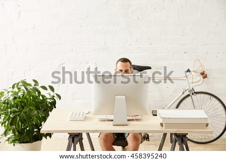 Worried freelancer works on his computer at home in summer time His vintage bicycle parked behind near the white brick wall and big green plant on side. - stock photo