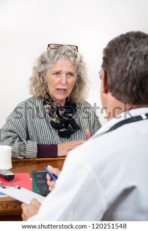 Worried frightened mature woman consults with doctor in his office. Focus on the woman. - stock photo
