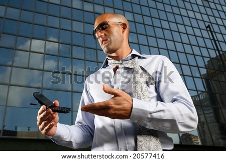 Worried, frustrated, freaked-out business man yelling at a cell phone on a business building background.