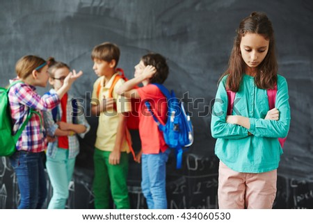 Worried girl standing alone from her classmates - stock photo