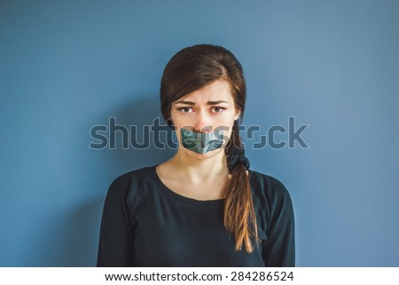 Worried girl with duct tape over her mouth - stock photo