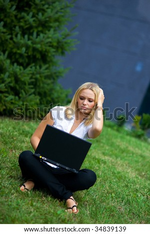 worried girl with laptop outside - stock photo