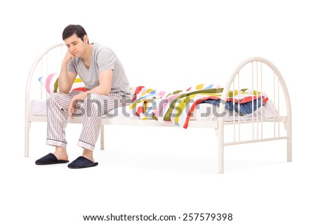 Worried guy sitting on a wooden bed isolated on white background - stock photo