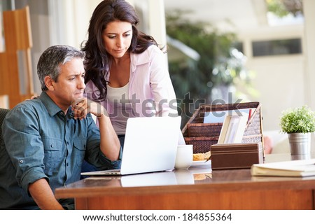 Worried Hispanic Couple Using Laptop On Desk At Home - stock photo