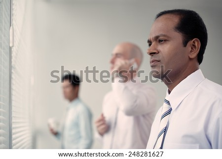 Worried Indian businessman looking through the window, his colleagues in background