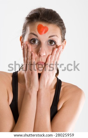 Worried looking woman with hands on face wearing a red heart on her forehead.