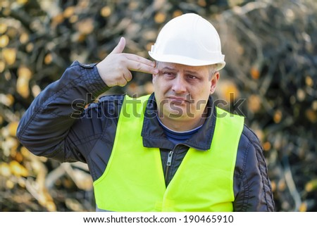 Worried lumberjack in forest near the branch pile - stock photo