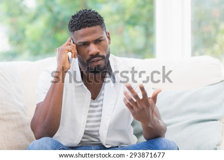 Worried man on the phone at home in the living room