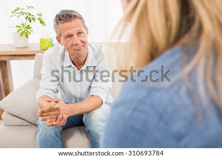 Worried man sitting on couch and talking to therapist in the office - stock photo