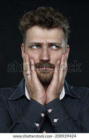 worried married handsome bearded man anxiously press his palm to face. close up portrait on dark background. Studio shot.