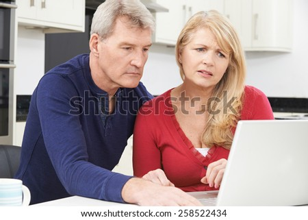Worried Mature Couple Reviewing Domestic Finances - stock photo