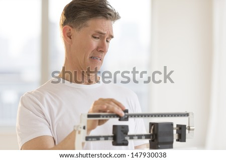 Worried mature man using balance weight scale at gym - stock photo