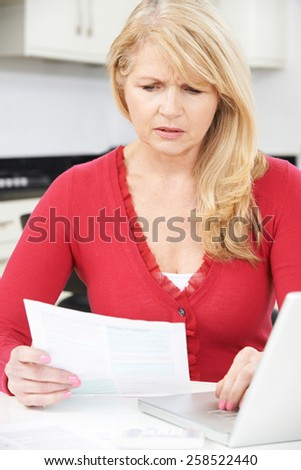 Worried Mature Woman Looking Reviewing Finances At Home