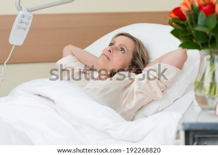 Worried middle-aged woman lying thinking in a hospital bed with her hands clasped behind her head as she stares at the ceiling with an intense expression - stock photo