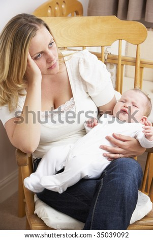 Worried Mother Holding Baby In Nursery - stock photo