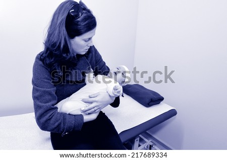 Worried mother holds her sick baby in hospital ward room. Concept photo of childhood , health care, medical treatment  and motherhood. (BW) copyspace - stock photo