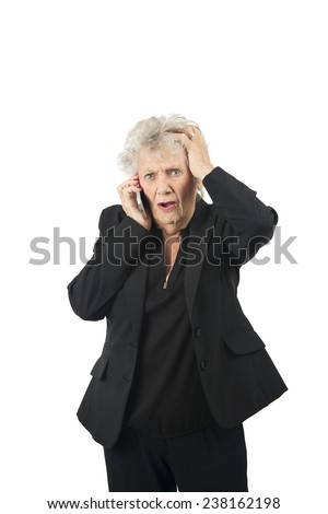 Worried old woman talking on her mobile phone against a white background - stock photo