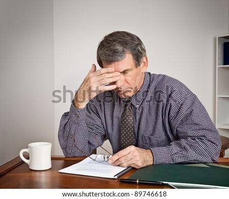 Worried, overworked businessman at desk - stock photo