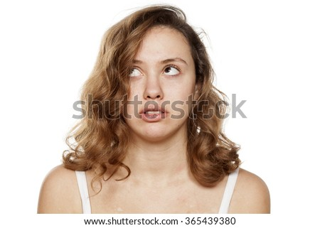 worried pensive young woman without make-up - stock photo