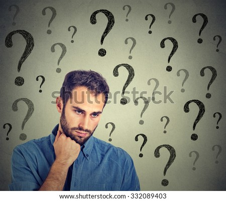 Worried sad man has many questions looking down isolated on gray wall background. Human face expression emotion feelings perception