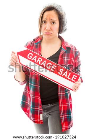 Worried saleswoman holding a garage sale sign - stock photo