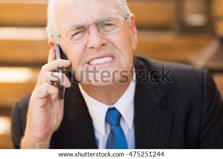 Worried Senior Businessman with Phone