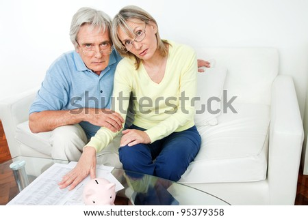 Worried senior couple with bills and piggy bank in living room - stock photo