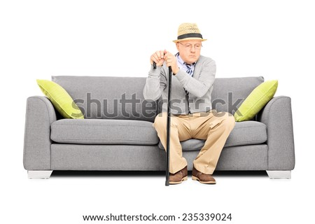 Worried senior gentleman sitting on a sofa isolated on white background - stock photo