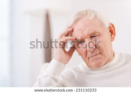 Worried senior man. Frustrated senior man touching his head while sitting in chair