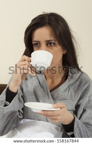 Worried - sick young woman sitting in bed with a hot drink. - stock photo