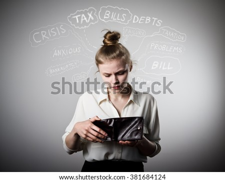 Worried slim woman is looking at an empty wallet. Poverty, taxes, debts and other problems. - stock photo