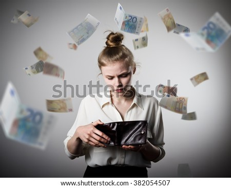 Worried slim woman is looking in a wallet. Euros are falling.