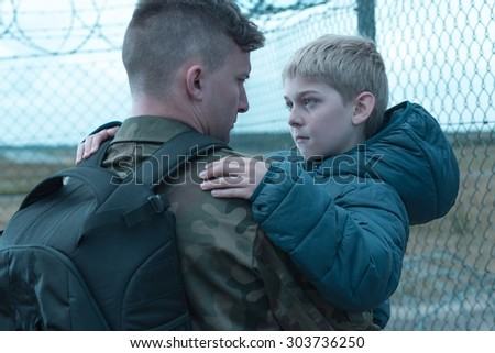 Worried son saying goodbye to his military father - stock photo
