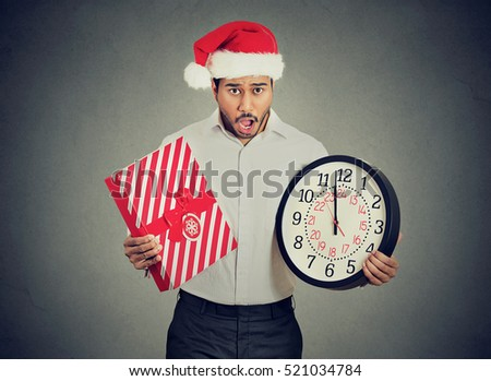 Worried stressed in a hurry young man wearing red santa claus hat holding clock gift box isolated gray background. Emotion, funny face expression, reaction. Last minute christmas holiday shopping
