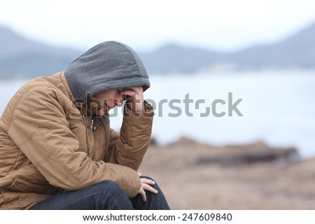 Worried teenager guy crying on the beach in winter in a bad weather day - stock photo