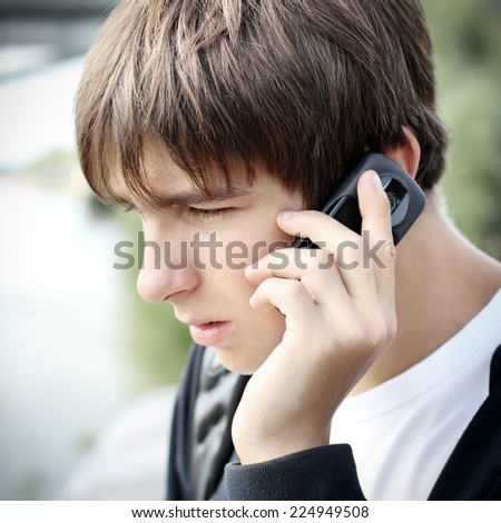 Worried Teenager speak by Cellphone outdoor - stock photo