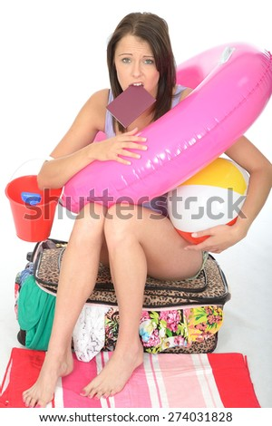 Worried Upset Young Woman on Holiday Holding a Passport with a Pink Rubber Ring Beach Ball and Bucket - stock photo