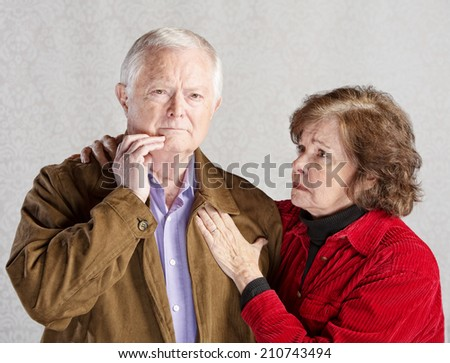 Worried wife holding concerned husband in jacket - stock photo