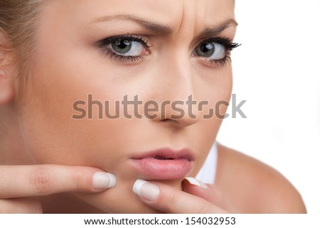 Worried woman. Disappointed young woman touching her face while isolated on white