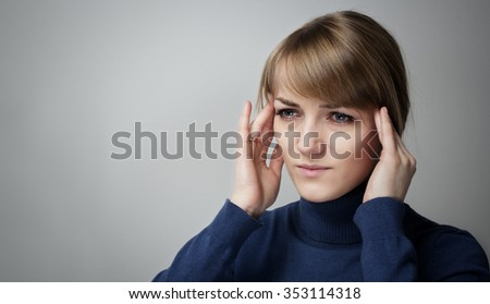Worried woman holding her head, migraine.Young woman with a wedding ring on his finger touching her head on grey background - stock photo