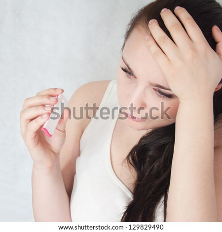 Worried woman holding pregnancy test - stock photo
