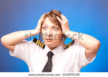 Worried woman pilot wearing uniform with epauletes looking ahead, standing on blue background. - stock photo