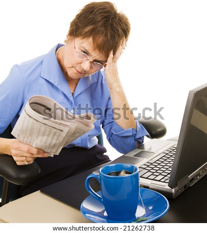 Worried woman reading the stock section of the newspaper.  White background. - stock photo