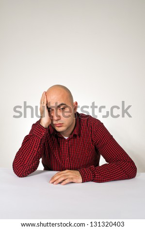 Worried young adult bald man sitting at the table with hand on his head.