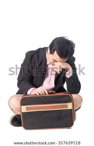 Worried young asian businessman with briefcase sitting in depression with hand on head, isolated on white background