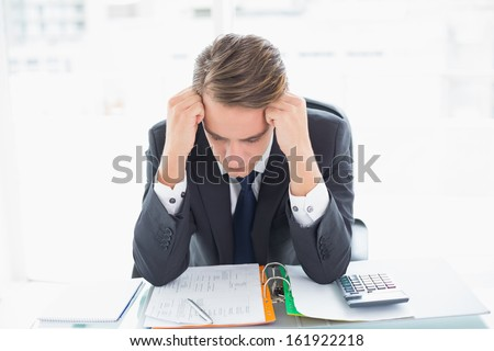 Worried young businessman looking down at documents in office - stock photo