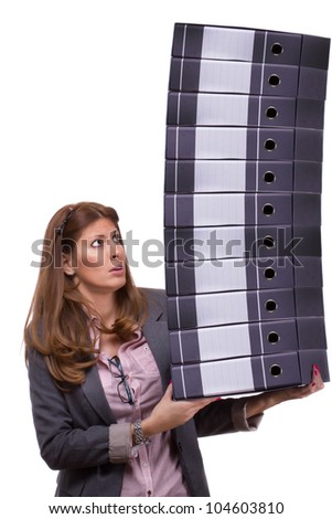 Worried young businesswoman holding a big pile of document ring binders, symbolizing work overload concept and exploitation by assigning too much work