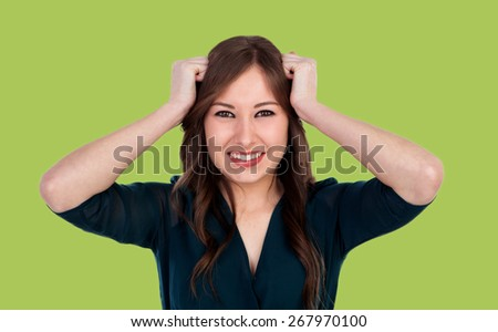 Worried young cool woman on a green background - stock photo